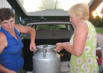 Vita ir Laima iškelia gardžiojo pienelio bidoną iš automobilio bagažinės.