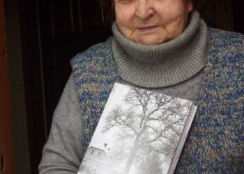 """Mokytoja Aldona Jagminienė glėbyje spaudžia knygą """"Butėnai""""."""