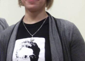 """Aistė Kučinskienė smagiai šypsosi – pasipuošusi Lietuvių kalbos ir literatūros instituto platinamais originaliais atributais – marškinėliais su Vaižganto atvaizdu ir citata: """"Eikš ant blaivinančio pašnekesio""""."""